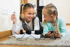 Sisters with socket extender Stock Photos