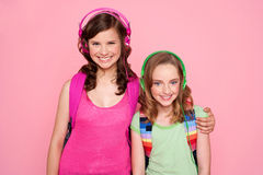 Sisters standing together and enjoying music Stock Image
