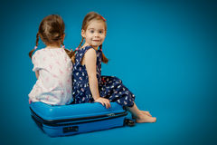 Sisters on a suitcase waiting for trip Royalty Free Stock Images