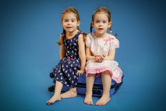 Sisters on a suitcase waiting for trip Royalty Free Stock Photography