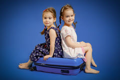 Sisters on a suitcase waiting for trip Royalty Free Stock Photos
