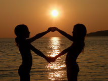 Sisters in summer sunset. Portrait of a young  sisters (twins) playing in summer sunset on sea. Two girls (best friends) to hold hands (spread) and singing a Royalty Free Stock Photo