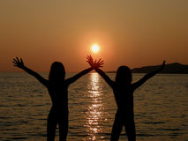 Sisters in sunset. Sisters with open arms in sunset on sea Stock Images