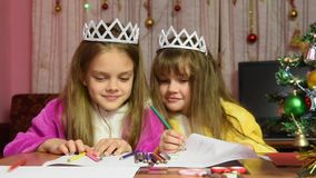 Sisters swearing and jostling drawing at a table in a Christmas setting stock video