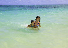 Sisters swimming in the ocean Stock Photography