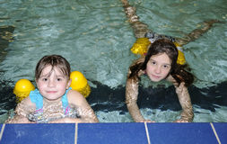 Sisters in swimming pool. Sisters swimming education in public swimming pool Royalty Free Stock Image
