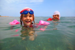 Sisters are swimming in sea. one girl in glasses Royalty Free Stock Image