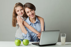 Sisters at the table with a laptop, milk and apple Stock Photo