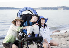 Sisters taking care of disabled brother on beach. Sisters taking care of disabled brother in wheelchair on beach Stock Photo