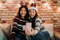 Sisters talking to parents by video chat app. Sisters talking to parents on cellphone using video chat app. two sisters celebrate xmas together at home. red stock photo