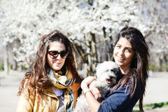 Sisters with their little dog Royalty Free Stock Photos