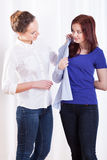 Sisters trying on shirt Stock Photos
