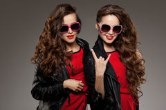 Sisters twins in hipster sun glasses laughing. Two fashion model. S. Women smiling and positive. Friends group having fun and talking. Youthful, friendship and Stock Photography