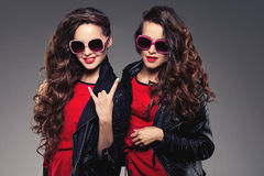 Sisters twins in hipster sun glasses laughing. Two fashion model Stock Photography