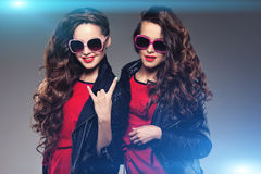 Sisters twins in hipster sun glasses laughing. Two fashion model Royalty Free Stock Photos