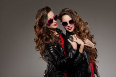 Sisters twins in hipster sun glasses laughing Two fashion models Stock Image