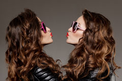 Sisters twins in hipster sun glasses laughing Two fashion models. Women smiling positive Friends group having fun, talking Youthful friendship youth adults Royalty Free Stock Photos