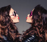 Sisters twins in hipster sun glasses laughing Two fashion models. Women smiling positive Friends group having fun, talking Youthful friendship youth adults Royalty Free Stock Images