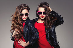 Sisters twins in hipster sun glasses laughing Two fashion models Royalty Free Stock Images