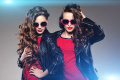 Sisters twins in hipster sun glasses laughing Two fashion models Stock Photos