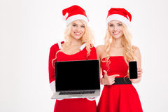 Sisters twins holding  mobile phone and laptop with blank screen Royalty Free Stock Photos