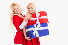 Sisters twins posing with presents in costumes of santa claus Royalty Free Stock Photos