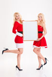 Sisters twins in red santa claus costumes holding blank board Royalty Free Stock Images