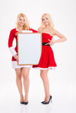 Sisters twins in red santa claus dresses with blank board Stock Photos