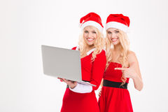 Sisters twins in santa claus clothes and hats with laptop Royalty Free Stock Photos