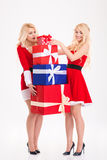 Sisters twins in santa claus costumes carrying heavy present box. Amusing pretty sisters twins in red santa claus costumes carrying heavy present boxes over Stock Images