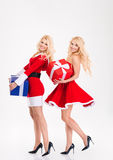 Sisters twins in santa claus costumes dancing with present boxes Royalty Free Stock Photos