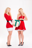 Sisters twins in santa claus costumes giving and getting gifts Stock Photography