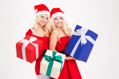 Sisters twins in santa claus costumes and hats holding presents Stock Photos