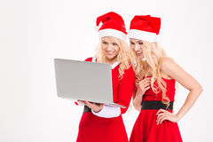 Sisters twins in santa claus costumes and hats using laptop Royalty Free Stock Photos