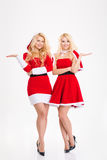 Sisters twins in santa claus costumes holding copyspace on palms Royalty Free Stock Images