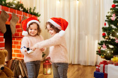 Sisters twins in Santa hats in a room with looking at Christmas Stock Photo