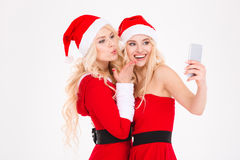 Sisters twins sending kiss and making selfie using mobile phone Stock Images