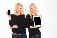 Sisters twins showing smartphone and tablet computer with blank screens Stock Images