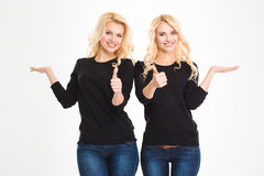Sisters twins showing thumbs up. Portrait of a smiling sisters twins showing thumbs up and holding copyspace on the palms isolated on a white background stock photos