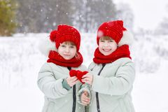 Sisters twins are showing two small hearts stock image