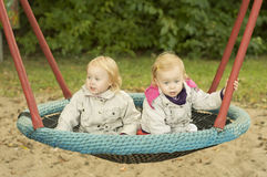 Sisters twins swinging on a swing. Girls twins have fun riding on a swing, in spring coats Royalty Free Stock Image