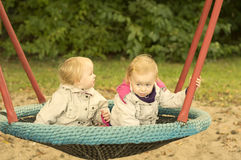 Sisters twins swinging on a swing. Girls twins have fun riding on a swing, in spring coats Stock Photo