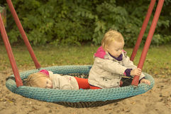 Sisters twins swinging on a swing. Girls twins have fun riding on a swing, in spring coats Stock Photography