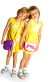 Sisters twins in yellow dresses Stock Photos