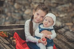 Sisters two with blue eyes wearing stylish village clothes posing on wooden old style retro wagon cart trundle with apples and red. Comforter plaid wrap happy Royalty Free Stock Image