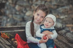 Sisters two with blue eyes wearing stylish village clothes posing on wooden old style retro wagon cart trundle with apples and red. Comforter plaid wrap happy Royalty Free Stock Images