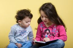 Sisters (two and four years old). Cute caucasian sisters reading a book. (two and four years old royalty free stock photos