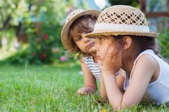 Sisters, two little girls on the grass, summertime, holidays. From school Royalty Free Stock Photography