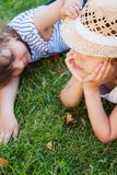 Sisters, two little girls on the grass, summertime, holidays royalty free stock images