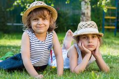 Sisters, two little girls on the grass, summertime, holidays. From school Royalty Free Stock Photo
